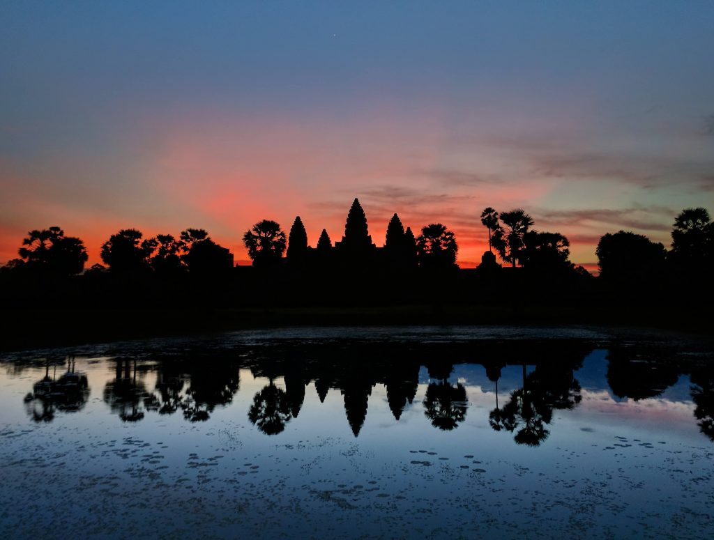 Composite of two sunset pictures of Anfkor Wat, one red and one blue