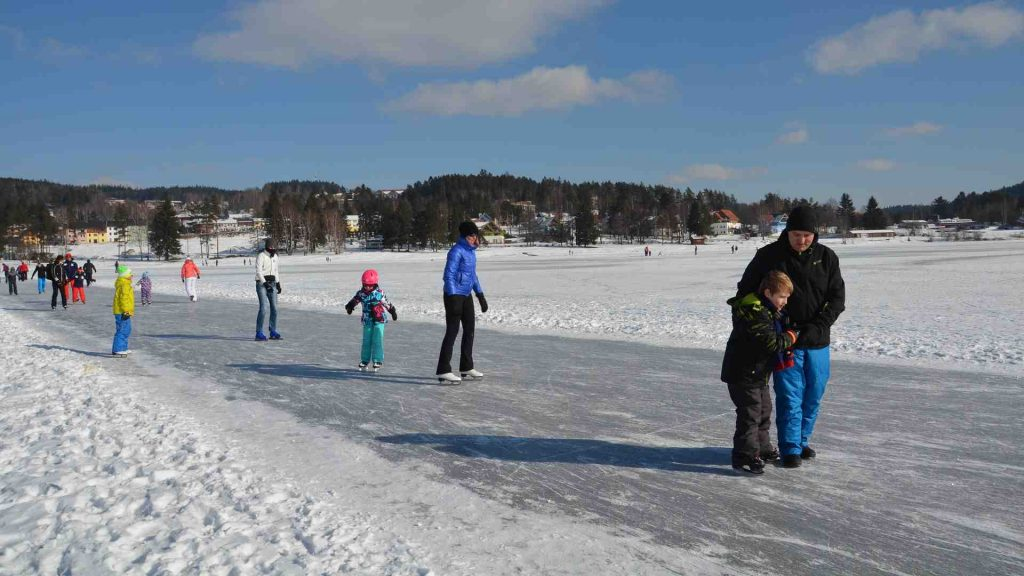 Ice skating on the frozen lake in Lipno nad Vltavou, Czech Republic, in winter