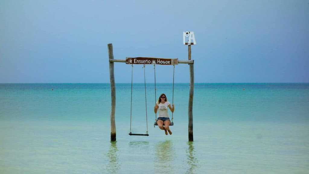 Ilona sitting on a swing in the water in Isla Holbox, Mexico
